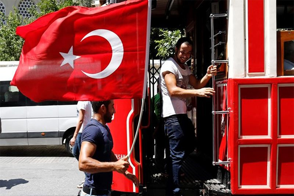 People travel with tram as they hold Turkish flag at the Taksim Square, as situation slowly gets back to normal after a coup attemp, in Istanbul, Turkey, 16 July 2016.  EPA/SEDAT SUNA People travel with tram as they hold Turkish flag at the Taksim Square, as situation slowly gets back to normal after a coup attemp, in Istanbul, Turkey, 16 July 2016. EPA/SEDAT SUNA